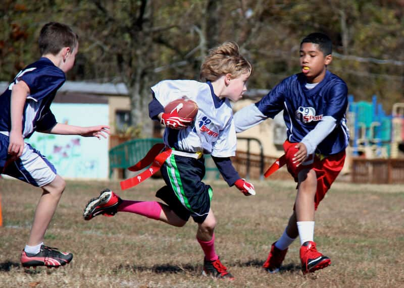 photo of boy running with football